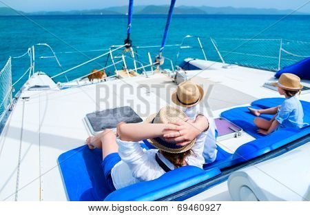Back view of mother and her kids relaxing having great time sailing at luxury yacht or catamaran boat