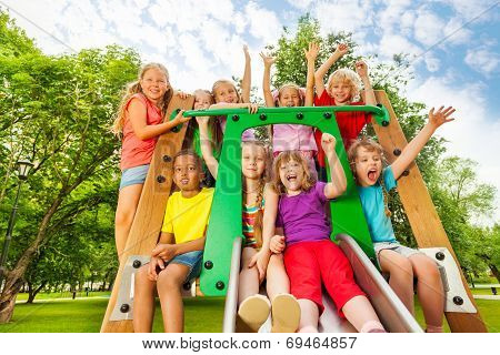 Excited kids on playground chute with arms up