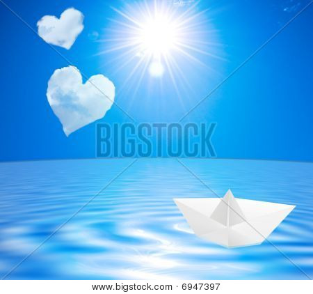 Sea Landscape With Clouds In The Form Of Hearts And A Paper Boat On Water