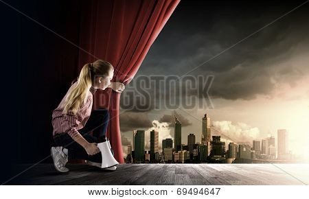 Young girl on stage with megaphone opening red curtain