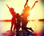 Beach Party. Teenage girls having fun in water. Group of happy young people dancing at the beach on beautiful summer sunset. Silhouettes of group of teen girls jumping and dancing. Joyful friends poster