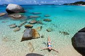 Above view of beautiful young woman relaxing floating in turquoise tropical water among granite boulders at Virgin Gorda, BVI, Caribbean poster