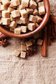 Brown sugar cubes and crystal sugar, spices in bowl on sackcloth background poster