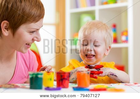 mom and kid boy painting together at home poster