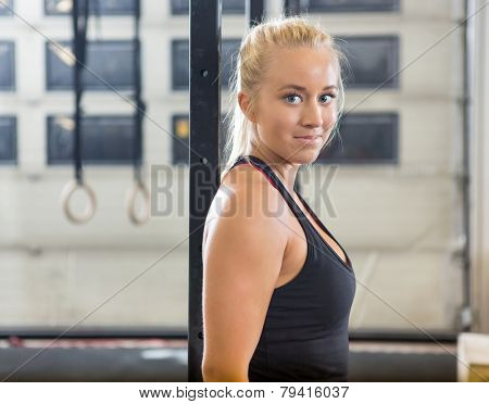 Side view portrait of confident fit woman standing at healthclub