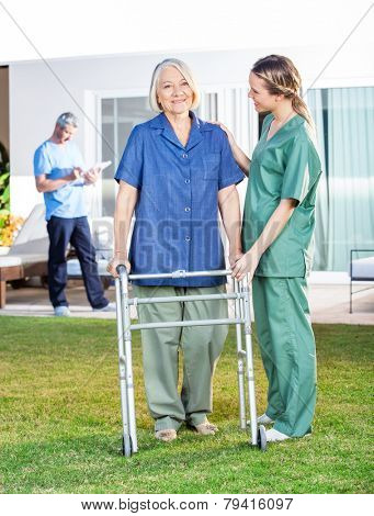 Female nurse helping senior woman to use walking frame in lawn with caretaker in background at nursing home