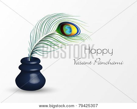 Glossy ink pot with peacock feather on white background for Happy Vasant Panchami celebration.