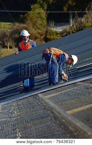 A builder screws down roofing iron for the roof on a large commercial building near Greymouth New Zealand poster
