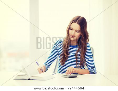 education and home concept - happy smiling student girl with notebook, calculator and book
