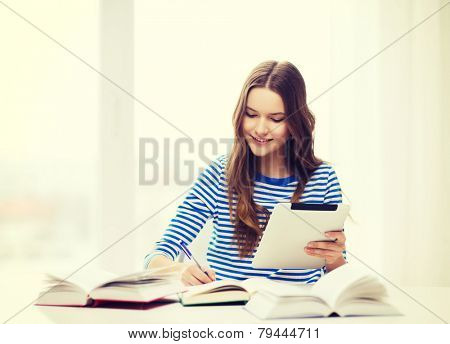 education, technology and home concept - happy smiling student girl with teablet pc computer and books at home