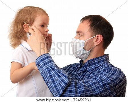 Dad puts a medical mask on to daughter.