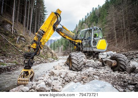 Wheeled excavator in a mountain river
