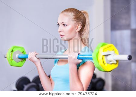 Young beautiful strong blond woman with barbell and weight plates