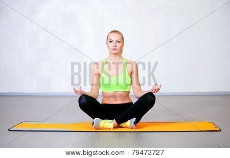 Young fitness woman doing yoga exercises sitting in lotus position