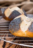 Homemade Pretzel Roll (with Poppyseed) on rustic wooden background poster