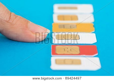 Close-up Of Hand Selecting Sim Card Over Blue Background poster
