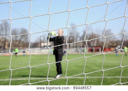 Image of a goalkeeper through the net. Women football poster