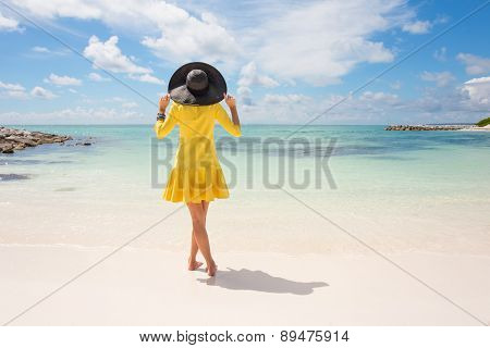 Fashionable woman with black summer hat and yellow dress on the beach