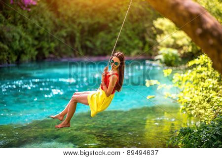 Woman swinging on the river