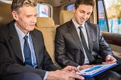 Two confident successful businessmen at a meeting sitting in the luxurious car and discussing churts. poster