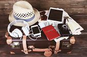 Packed suitcase of vacation items on wooden background poster