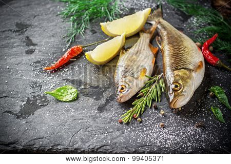Fresh fish ide on a black stone slab surrounded by herbs, slices of lemon