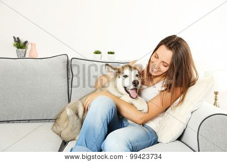 Woman sitting with her malamute dog on sofa in room