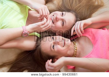 Closeup picture of two excited teenage blonde and brunette girls