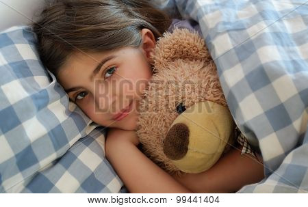 Girl Lying In Bed Hugging Her Teddybear