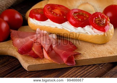Slice Of Prosciutto Ham On Chopping Board With Fresh Baguette