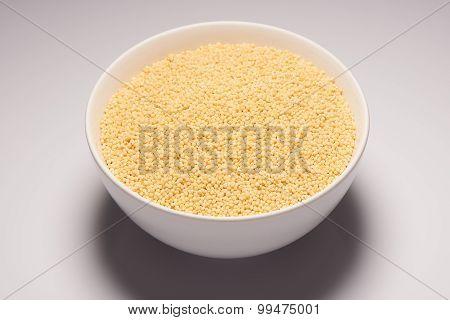 Raw organic millet croup in white ceramic bowl