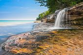 Elliot Falls is a small but beautiful waterfall that cascades over rocky ledges into Lake Superior at Pictured Rocks National Lakeshore near Munising Michigan. poster