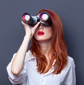 Portrait of a surprised businesswomen in white shirt with binocular on grey background. poster