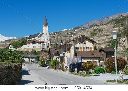 View to the residential area buildings and church from the street of Brig (Brig-Glis), Switzerland.