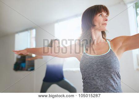 Women Exercising At Yoga Class.