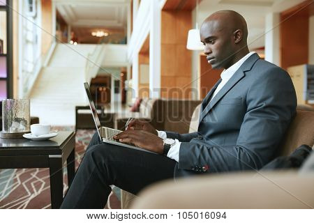 Busy Young Businessman Working On Laptop In Lobby