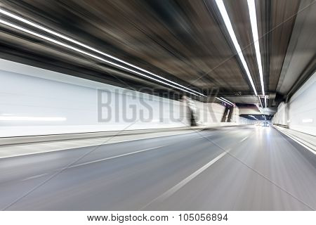 Abstract speed motion in highway road tunnel, blurred motion toward the central
