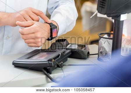 Closeup of male customer paying through smartwatch at counter in pharmacy