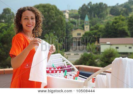 woman dressed in red dress hangs clean wear on balcony