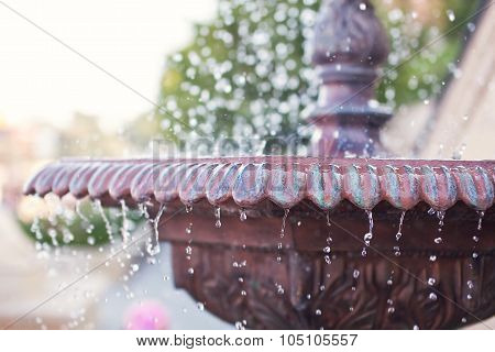 Close-up of an old stone fountain with dripping water on blurred background