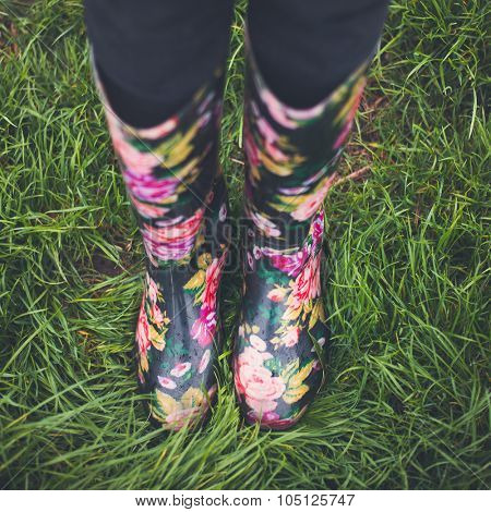 Autumn fall concept with green grass and rain boots outside. Close up of woman feet walking in rainboots.