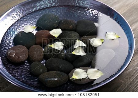Flower petals in plate with water and spa stones closeup