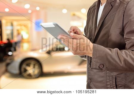 Young Businessman Using Tablet Device With Modern Sportcar