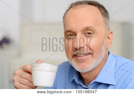 Agreeable man drinking tea.