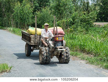 Asian Man Riding Farm Vehicle