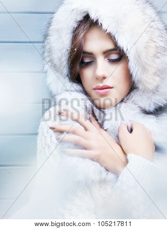 Beautiful young  brunette woman with eyes closed, wearing knitted sweater and fur hood, covered with snow flakes. Snowing winter beauty concept.