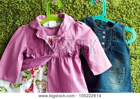 Fashion Baby Dress And Coat  Hanging On A Hanger On A Green Summer Background