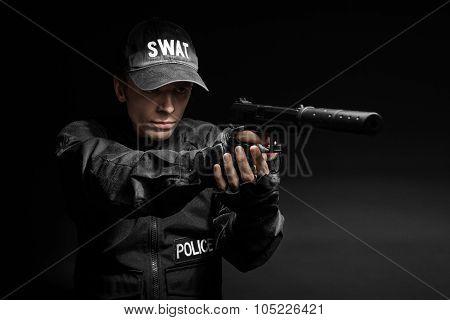 Spec ops police officer SWAT in black uniform with pistol studio poster
