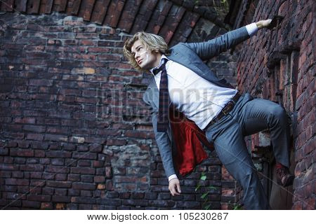 Businessman warrior. Young man  with  war paint on his face climbs up the wall , concept