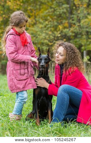 Little curly girl and her mother are caress the dobermann in park.
